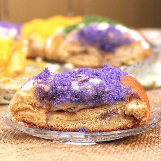 A slice of King Cake that is topped with white glaze and purple sanding sugar