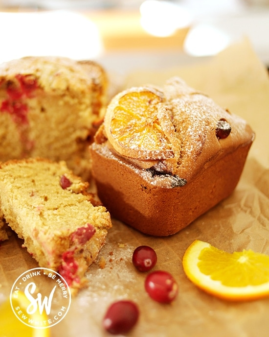 cranberry and orange loaf surrounded by fresh cranberries and orange slices