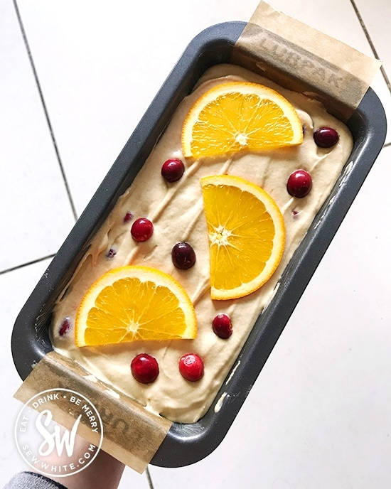 Oven ready orange and cranberry cake ready to be baked in the oven.