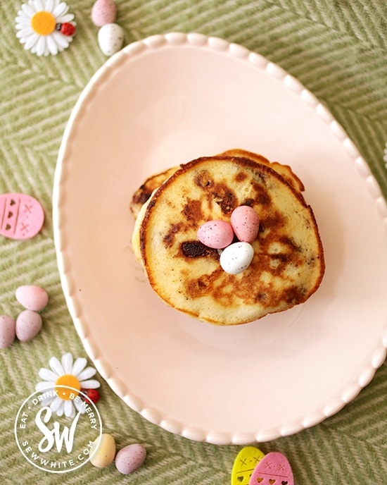 Easy Mini Egg Pancakes on a pastel pink Egg shaped plate surrounded by eggs and flowers.