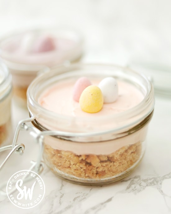 Picnic cheesecakes in little glass jars with mini eggs on top.