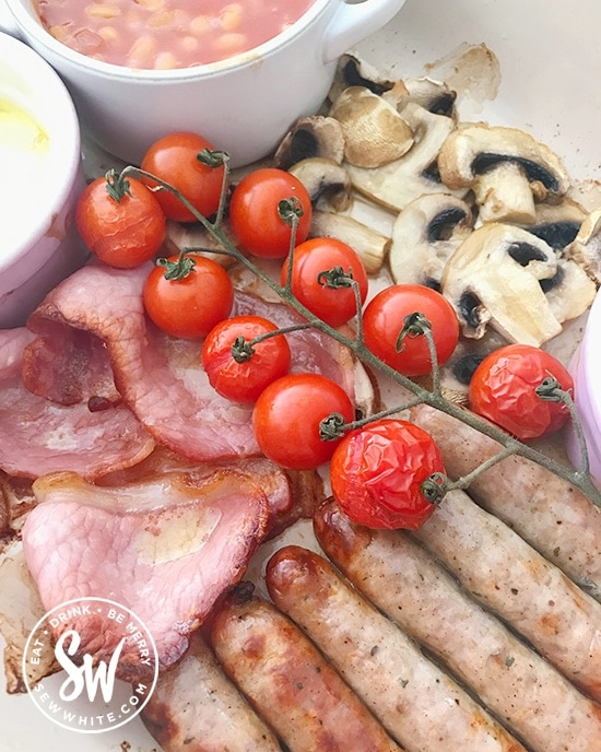 Close up of oven roasted tomatoes on top of cooked sausages, bacon and mushrooms in the full english breakfast traybake