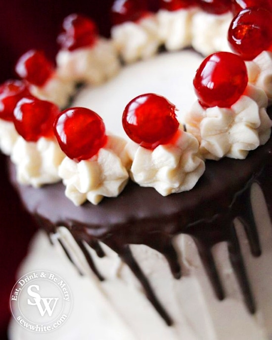 easy black forest layer cake with chocolate drip and glace cherries as decoration