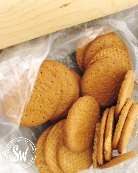 digestives biscuits in a bag with a rolling pin to be turned into a crumb