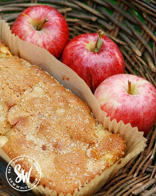 rosy red apples next to the freshly baked apple ginger loaf cake