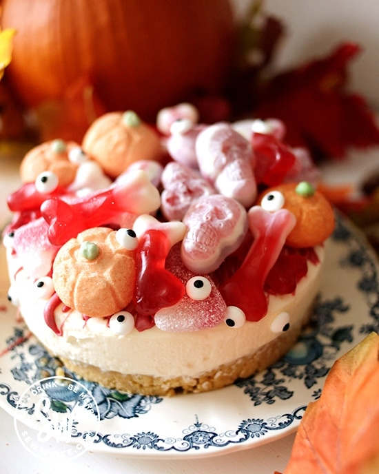 Halloween cheesecake covered with candy and edible eye sprinkles and edible pumpkins marshmallows