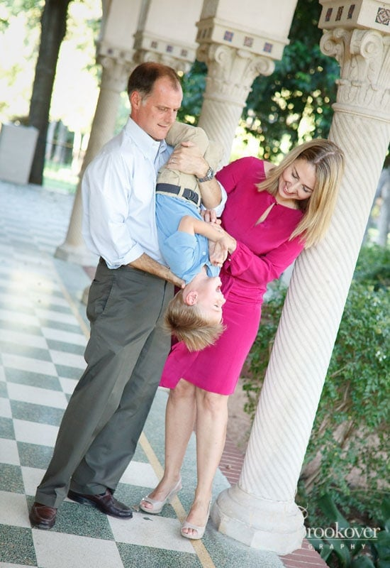 mom and dad laughing with son on the steps of Landa Library