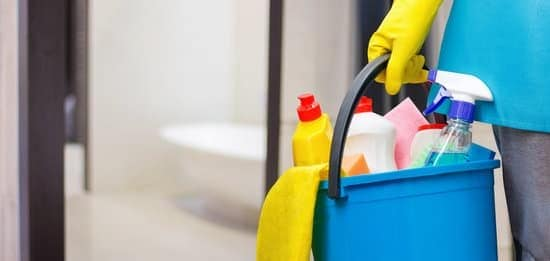 hand holding bucket of cleaning supplies to make home look better