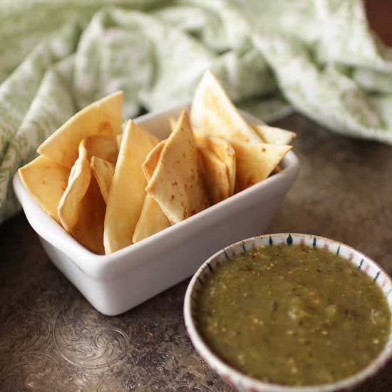 Baked Tortilla Chips in serving dish with green salsa in a bowl
