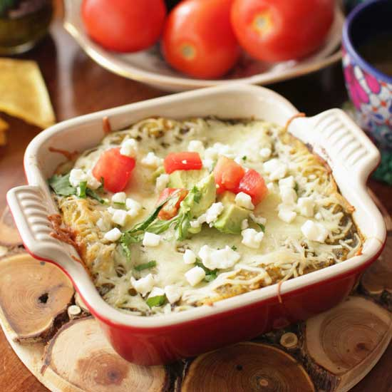 enchiladas verdes in a red baking dish next to a bowl of tomatoes.