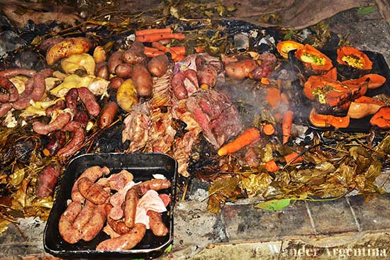 Curanto preparation involves cooking meat and vegetable wrapped in leaves over hot stones
