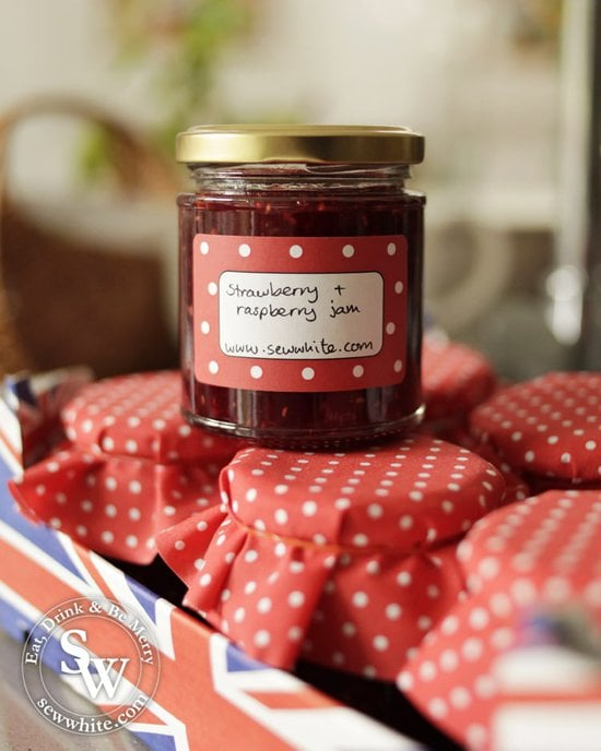 Strawberry and Raspberry Jam in glass jars with red fabric covers.