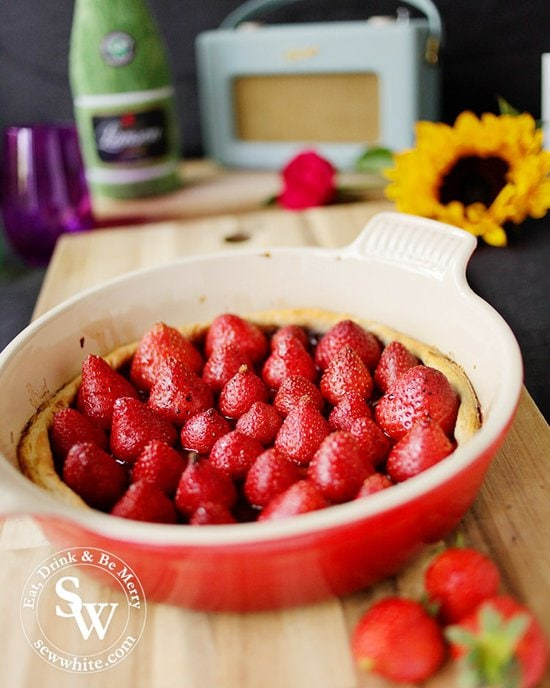 Rich red strawberries in a gold tart crust in the le creuset round stoneware dish for my Balsamic Vanilla Strawberry Tart.