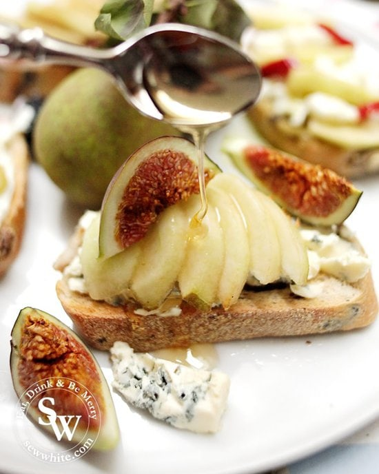 Pears on toast with blue cheese and figs being drizzled with honey.