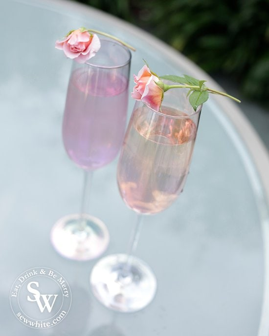 Irredentist purple and pink champagne glasses with roses balanced on top  for the Prosecco cocktail