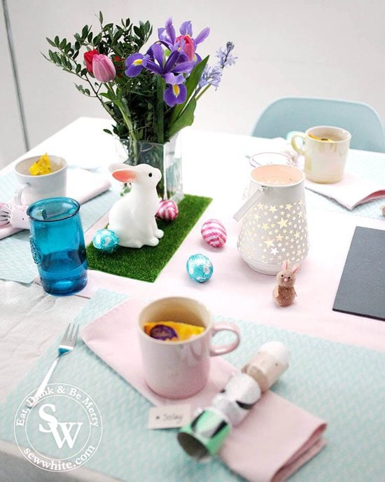 Easter Table Inspiration with pastel pink, blue and purples. Fresh flowers and little rabbits on fake grass.