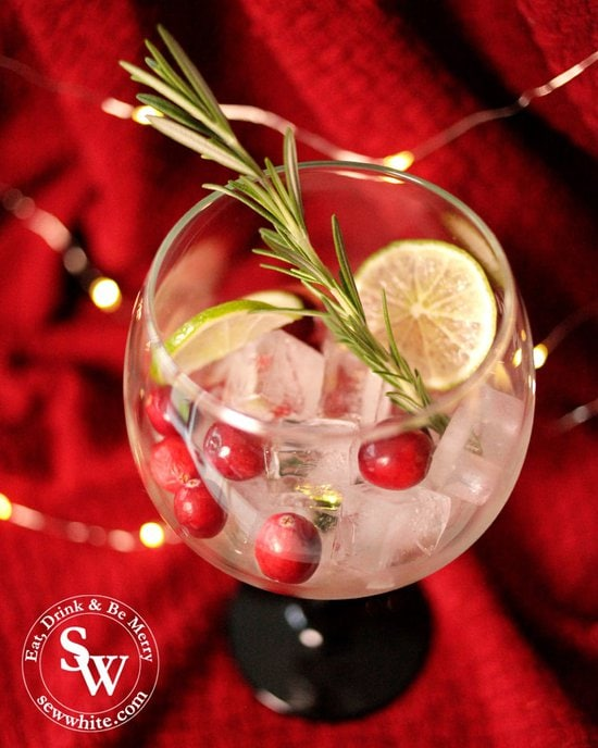 Making up a beautiful Christmas gin cocktail with fresh cranberries, rosemary and lime for the Christmas Cranberry Gin Cocktail