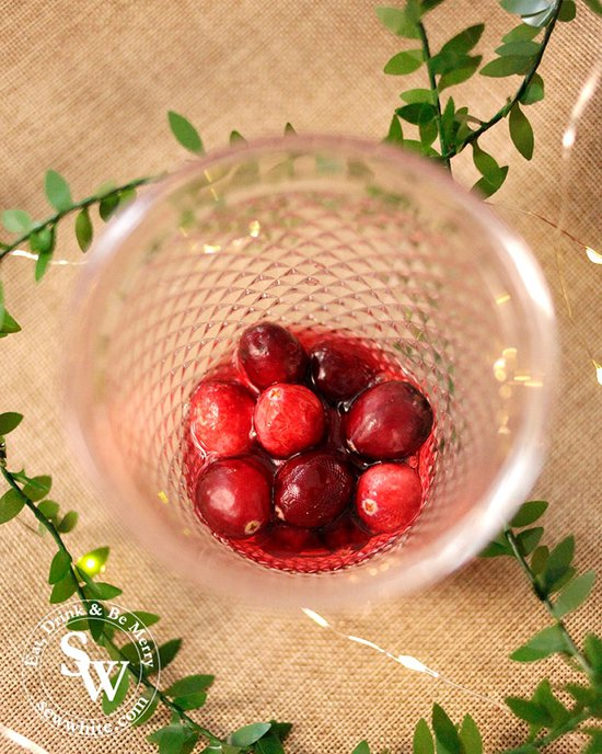 fresh cranberries in the bottom of a glass with cranberry liqueur