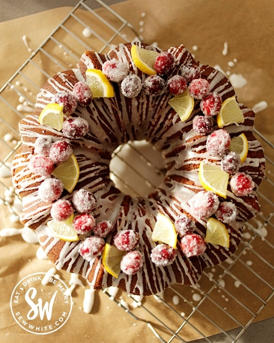 Top view of the Cranberry and Lemon Bundt Cake topped with dusted cranberries and lemon slices