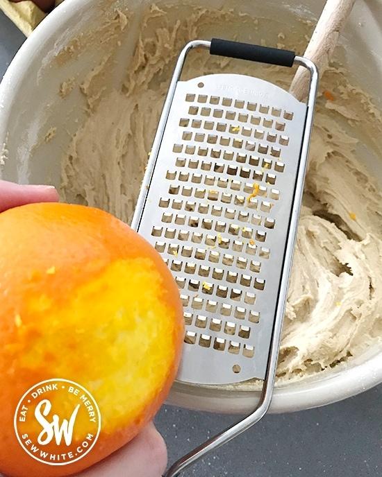 grating orange zest into the cake mix