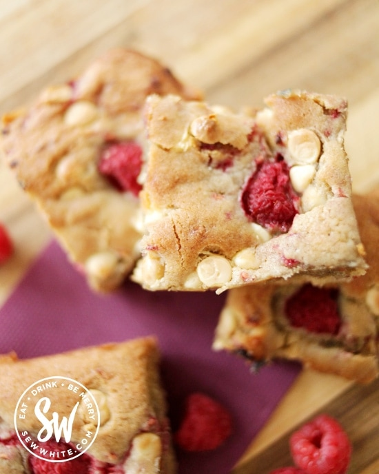 golden baked raspberry white chocolate cookie traybake on a purple napkin and wooden bench.