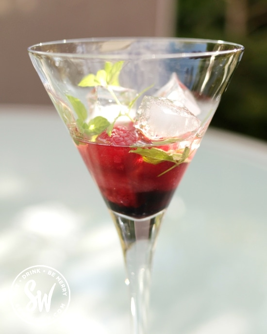 cocktail glass with mint, raspberries and ice cubes