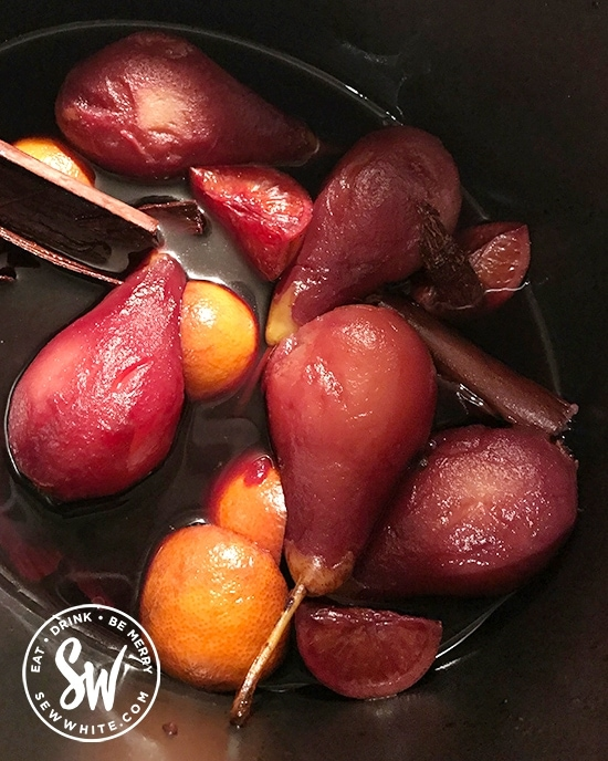 mulled wine pears in a slow cooker dyed red from the wine