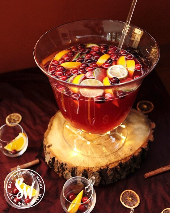 Red Christmas Punch with fresh cranberries and orange slices in for decorations on a red table.