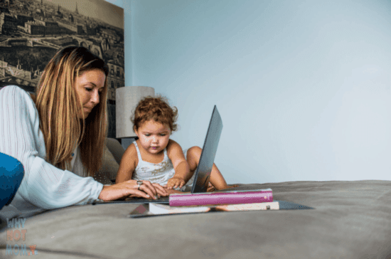 mother working on her laptop with her toddler daughter next to her sitting on the bed