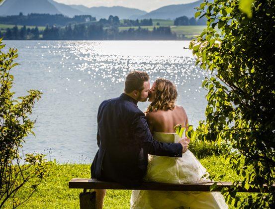 Hochzeitsfotograf Kempten Hochzeitspaar Kuss Hopfensee Parkbank