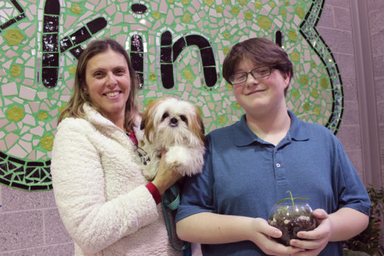 An image of student Aidan with social worker Toni and dog Leo
