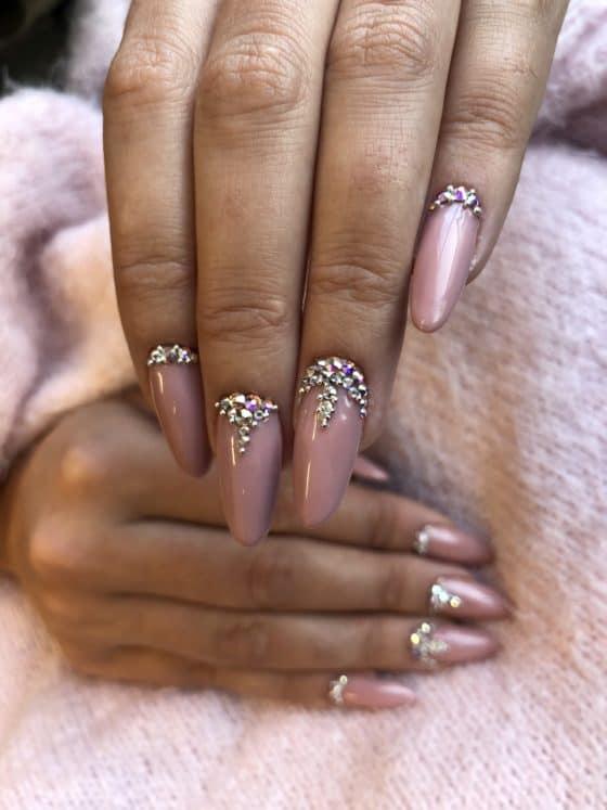 różowe mataliczne paznokcie hybrydowe z ozdobą z cyrkonii