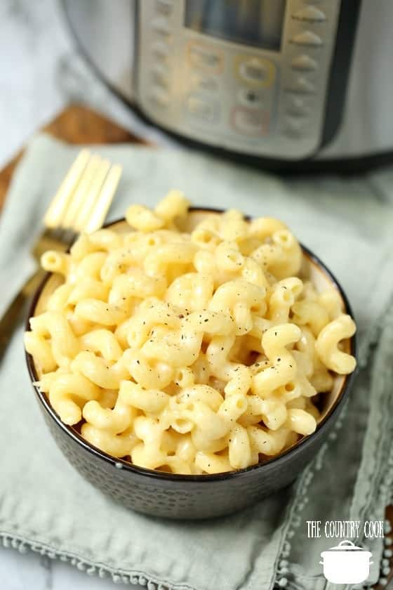 Instant Pot White Cheddar Macaroni and cheese in a bowl with electric pressure cooker in the background
