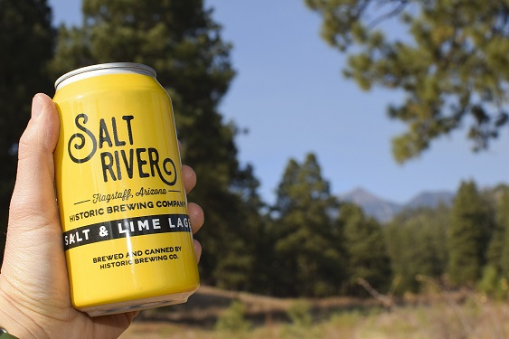 hAND HOLDS YELLO CAN OF fLAGSTAFF CRAFT BEER in foreground. Backgrouns is forest of Ponderosa pines found around Flagstaff