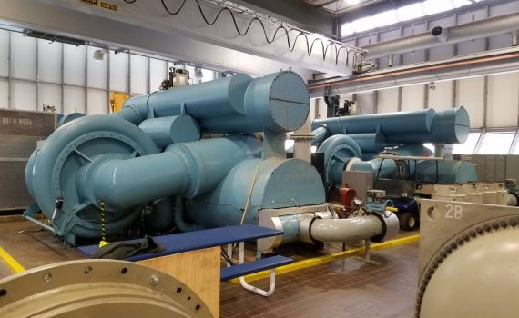 Two dark green centrifugal chillers undergoing maintenance in plant room
