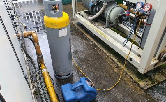 Blue recovery unit with a grey recovery cylinder during a chiller breakdown