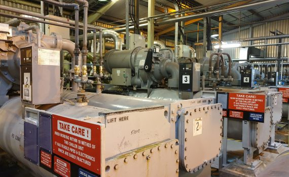 Chilling plant maintenance of grey machines with red warning signs