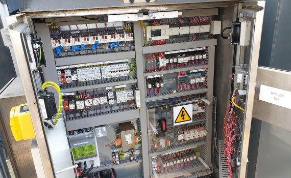 Open chiller controls panel showing PLC, relays, contactors and wiring