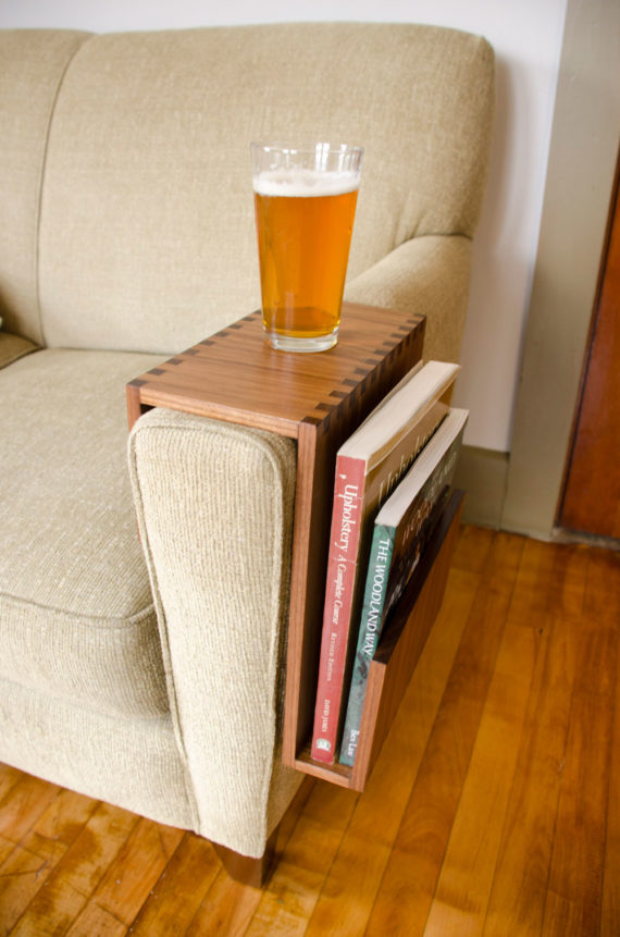 couch arm table with book pocket shown in walnut wood