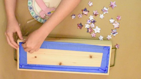 Blue painter's tape on bottom of decorative tray for prep