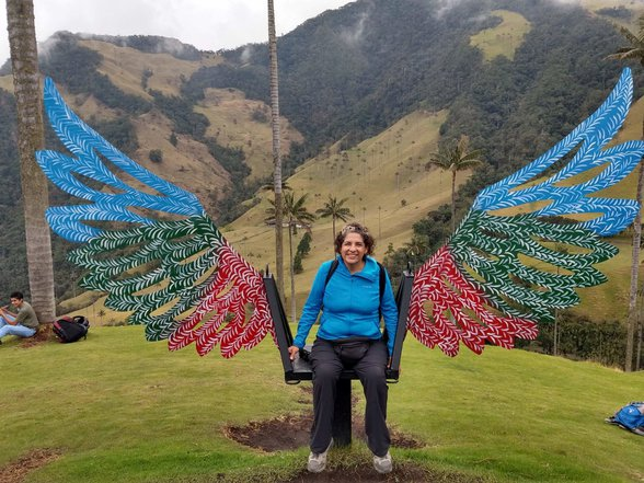 Charo sitting with angel wings behind her Cocora valley