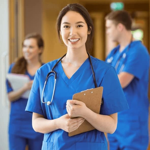 A smiling young woman in blue scrubs holding a clipboard with a stethoscope around her neck.