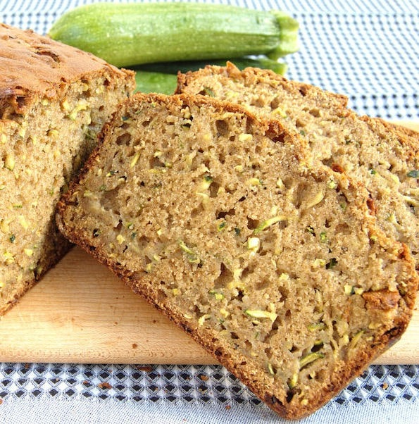 a slice of whole wheat zucchini bread with zucchinis in the background