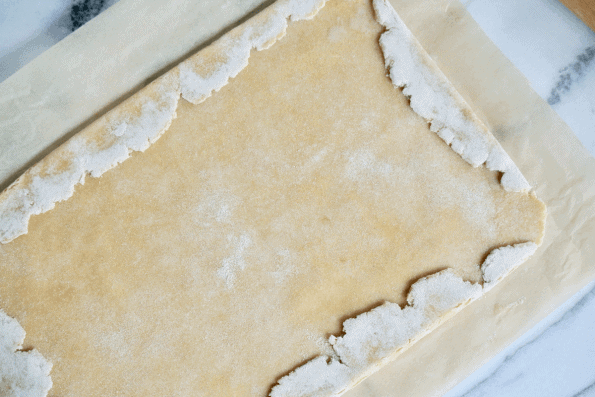 Folding the ragged Sourdough pastry edges over to form a straight sided rectangle.