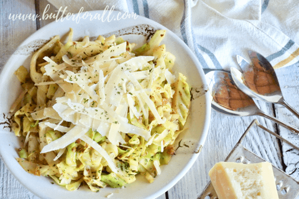 A beautiful bowl of keto friendly cabbage noodles is flavored with extra garlic butter and topped with fresh shaved parmesan cheese.
