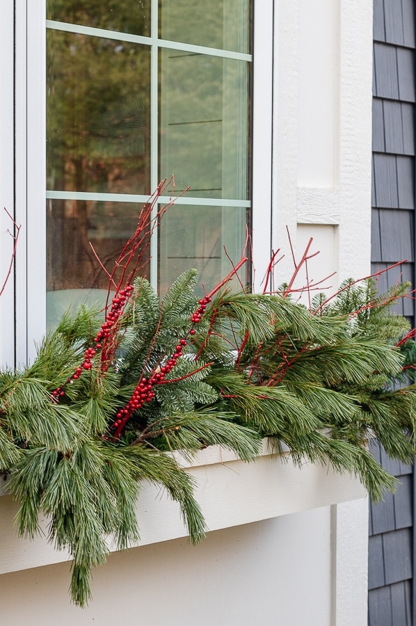 Cedar and red winter berries in window boxes.