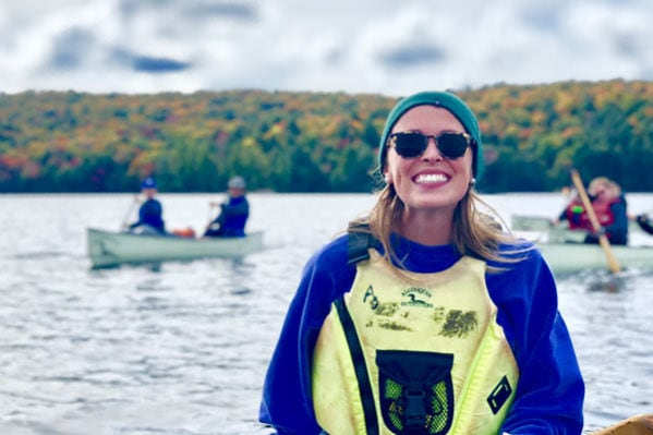 student smiling in life vest with canoes in background