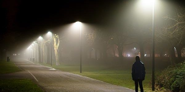 person standing under street lights at night