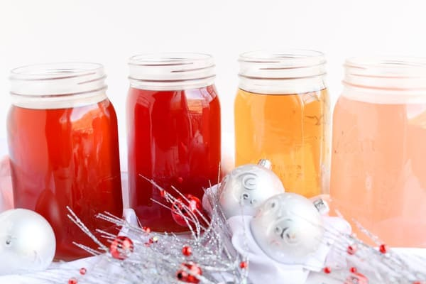 Four jars of holiday infused water with christmas decorations