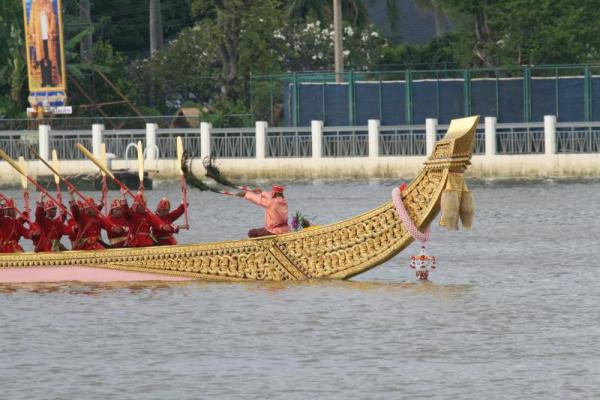 "Barge Master waves black feather ""batons"" at oarsmen dressed in red traditional Thai uniforms. Oarsmen raise paddles in unison during Royal Water Processional."
